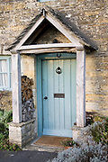 Front door and porch of typical Cotswolds cottage in village in Oxfordshire, England, United Kingdom