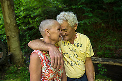 "Charlie Branham, a former coal miner, poses with his wife Donna outside their home in Lenore, West Virginia. Donna Branham shaved her head on the steps of the West Virginia Capitol with a group of women in protest to mountaintop-removal mining. The shaving of their heads was symbolic of the mountains that have been stripped of all of the living things on them. It was also symbolic of the many people who are sick or dying as the result of Mountaintop Removal. Mountaintop Removal is a method of surface mining that literally removes the tops of mountains to get to the coal seams beneath. It is the most profitable mining technique available because it is performed quickly, cheaply and comes with hefty economic benefits for the mining companies, most of which are located out of state. It is the most profitable mining technique available because it is performed quickly, cheaply and comes with hefty economic benefits for the mining companies, most of which are located out of state. Many argue that they have brought wage-paying jobs and modern amenities to Appalachia, but others say they have only demolished an estimated 1.4 million acres of forested hills, buried an estimated 2,000 miles of streams, poisoned drinking water, and wiped whole towns from the map. ""People don't know how hard it is on the Appalachian people,"" Branham said of mountaintop-removal mining. ""They have no idea. And they don't want to know. As long as they don't have to look at it, they can ignore it."" © Ami Vitale"