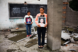 Zhao Xiao Qiong, 36, holding a picture of  daughter Lan Xiao Juan, 10, right, and Yang Zai Yin, holding a picture of  son Liu Chao, 12, are seen  at Fuxin No.2 Primary  School in Wufu, Sichuan province. Both mothers have only one child.