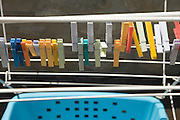clothes pegs on a drying rack with wash basket under it