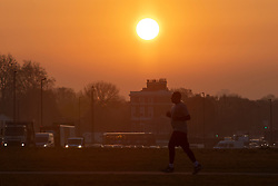 © Licensed to London News Pictures. 20/04/2021. London, UK. A man jogs during sunrise on Blackheath Common in South East London. Temperatures are expected to rise with highs of 16 degrees forecasted for parts of London and South East England today . Photo credit: George Cracknell Wright/LNP