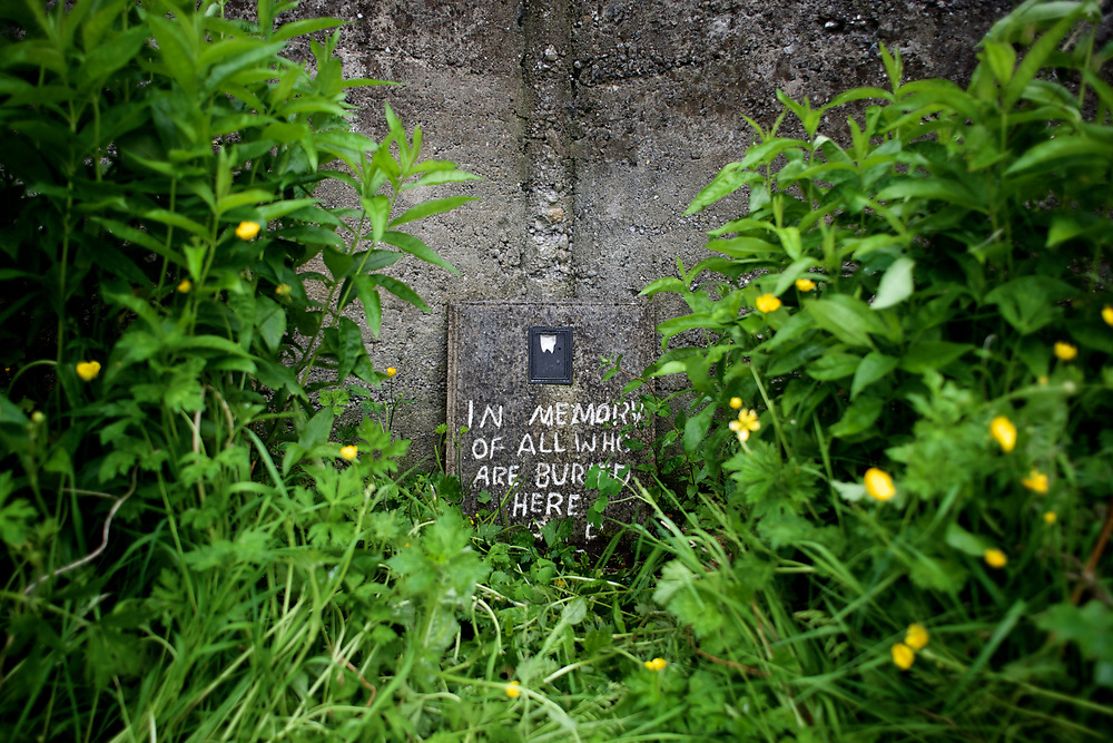 A memorial plaque is seen among vegetation in a corner of the grave site where Catherine Corless, a local historian from Tuam, claims to be the resting place of 796 children, most of them infants, who died between 1925 and 1961 at the 'Home', a old single mother and baby orphanage called St. Mary's, run by Sisters of Bons Secours. The story that emerged from Corless's research has been reported in recent weeks in dramatic headlines around the world, with many describing the site, used in the past as a septic tank for the orphanage, as a mass grave.