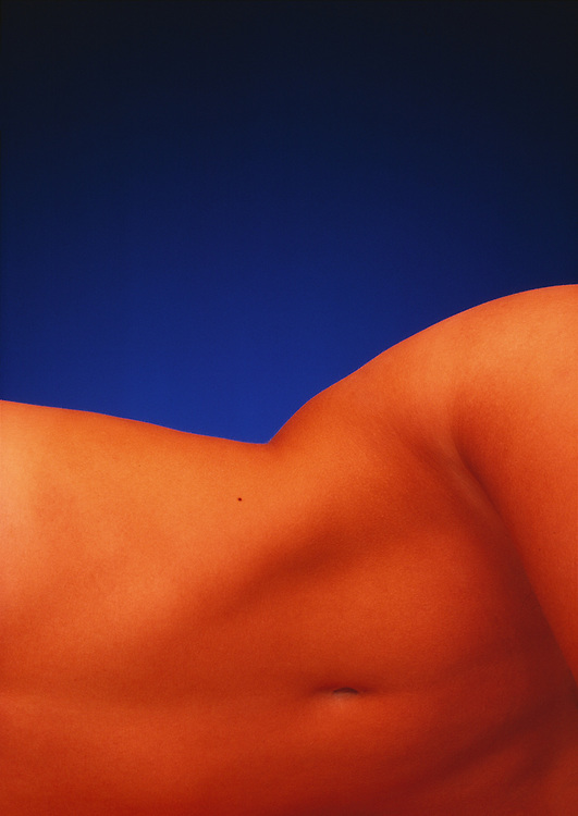 Reclining nude woman's slim torso with rich orange light and a vibrant blue background