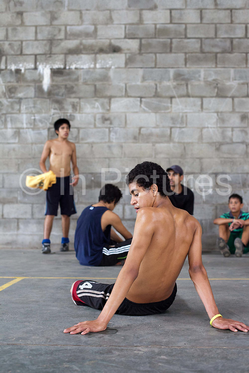 Young boys men teenagers sitting and listening to their coach after playing football on a concrete pitch court, at La Casita home for disadvantaged or recovering street children, Buenos Aires, Argentina. This group were the Argentinian 'Street Child World Cup' team held in Rio de Janeiro in March 2014.
