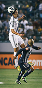 Los Angeles Galaxy defender Omar Gonzalez, left, heads the ball away from Monterrey forward Humberto Suazo during the first half of the CONCACAF Champions League semifinal, Wednesday, April 3, 2013, in Carson, Calif. (AP Photo/Bret Hartman)