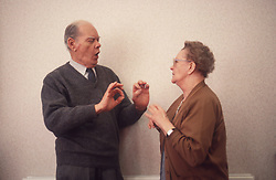 Elderly couple with hearing impairments using sign language to communicate,