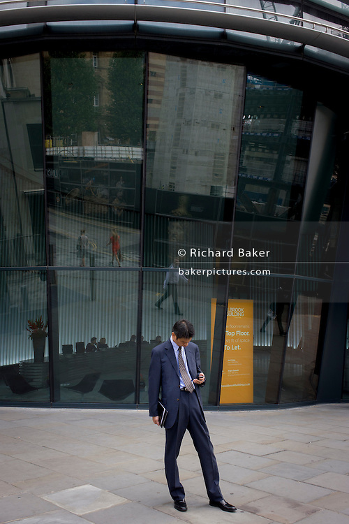 Businessman checks messages beneath modern office entrance architecture on Walbrook, City of London.