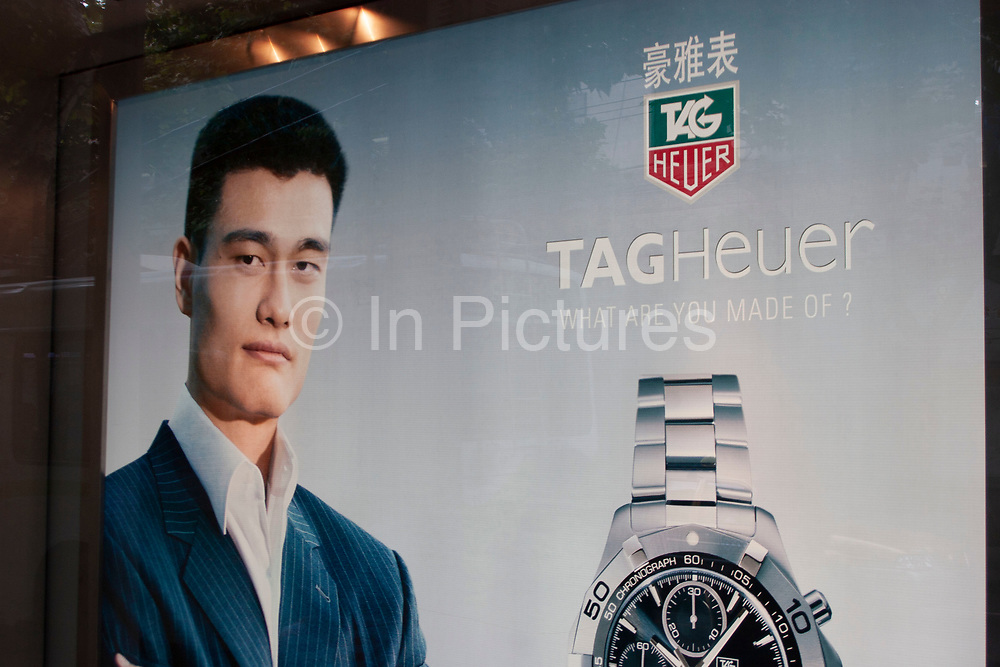 Chinese NBA basketball player Yao Ming uses his image to endorse Tag Heuer watches in this advertisement in a designer shop window on Nanjing Road, one of Shanghai's most fashionable and expensive shopping districts. High end fashion has joined the many high street stores as Shanghai becomes wealthier. This road with its expensive hotels and consulates is one area where these shops are common. As in Hong Kong where designer fashion outlets fill some shopping malls, Shanghai is heading the same direction.