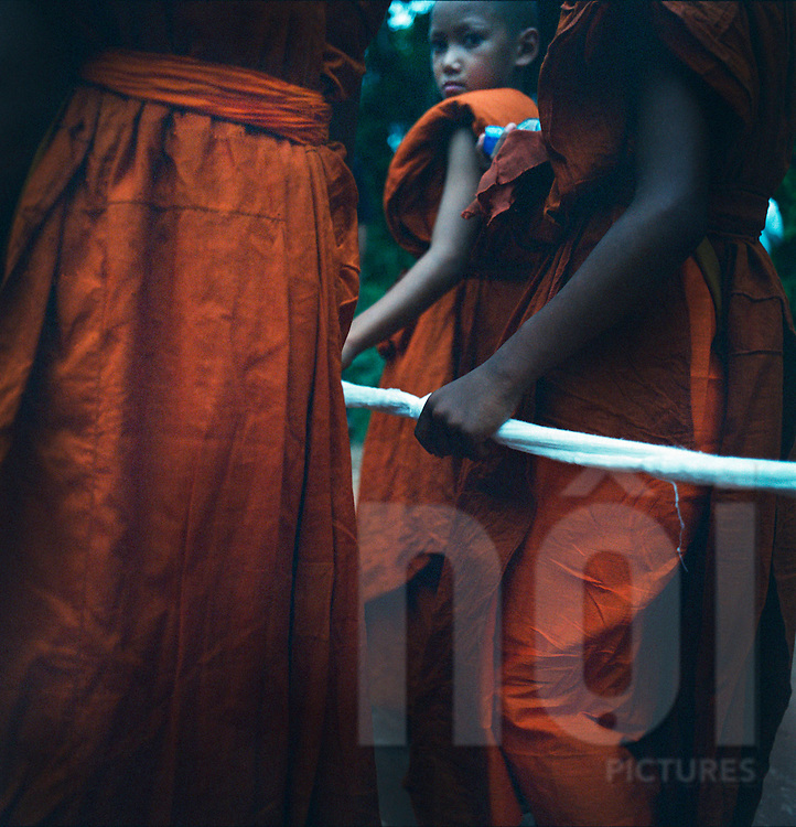 Funeral ceremony, Vientiane Province, Laos. Buddhist monks with their traditional orange robe handle a a white rope in their hand