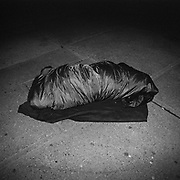 A homeless person in a sleeping bag on top of a heated exhaust vent for an office tower on Melinda Street in Toronto's Financial District..(Credit Image: © Louie Palu/ZUMA Press)