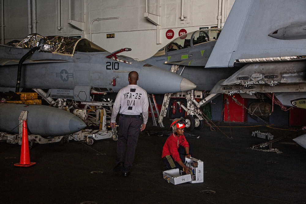 Crew members with F/A-18 Hornets on the hanger deck, where aircraft are stored and repaired<br /> <br /> Aboard the USS Harry S. Truman operating in the Persian Gulf. February 25, 2016.<br /> <br /> Matt Lutton / Boreal Collective for Mashable