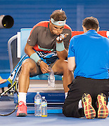 Rafael Nadal of Spain faced Roger Federer of Switzerland in the 2014 Australian Open Mens Singles semifinals. Nadal won the match 7-6, 6-3, 6-3. Nadal faces S. Wawrinka of Switzerland in Sunday's finals.The match was held at Melbourne's Rod Laver Arena. Here, Nadal blows on the medication used to treat massive blisters on his left hand.