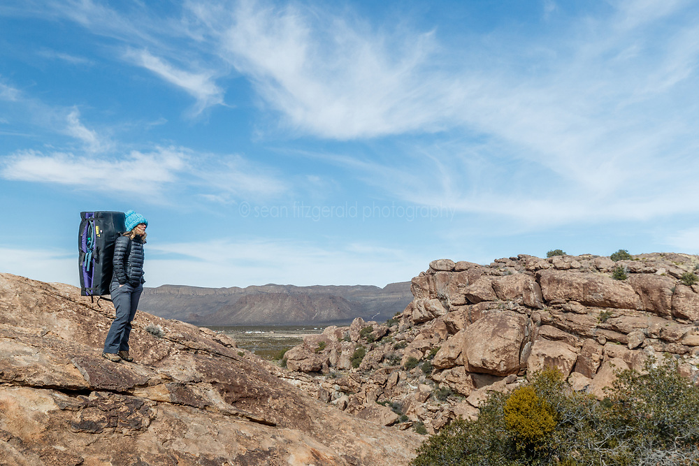 Sarah Hepola viewing landscape and canyons while carrying bouldering pads to climbing site, Hueco Tanks State Park & Historic Site, El Paso, Texas. USA.