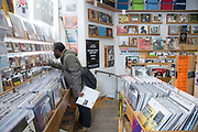 A man searching for vinyl in a record shop on the 23rd March 2018 in Soho London in the United Kingdom.