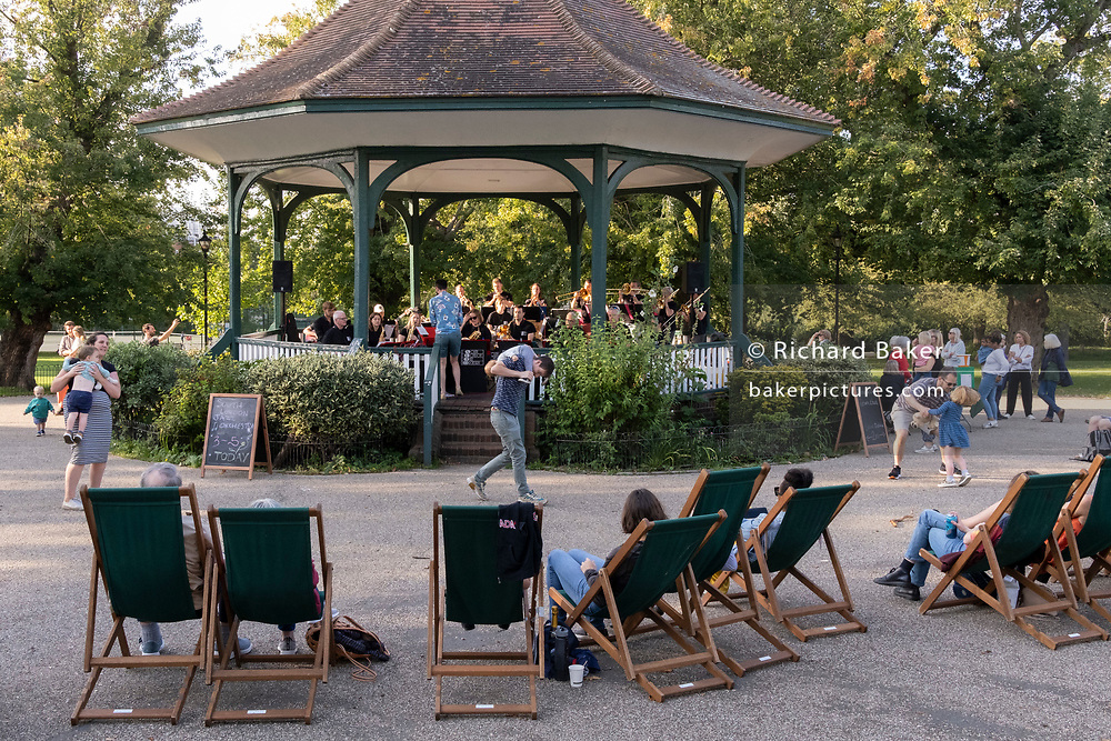 South London parents dance with children to the music of the South London Jazz Orchestra at the bandstand in Ruskin Park, on 26th September 2021, in London, England.