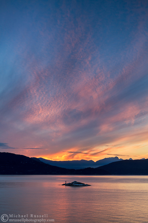 One of the Grebe Islets in Howe Sound, Bowen Island, and mountain peaks in the Sunshine Coast's Tetrahedron Range at sunset.  Photographed from Juniper Point at Lighthouse Park in West Vancouver, British Columbia, Canada.