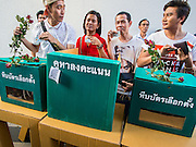 """14 FEBRUARY 2015 - BANGKOK, THAILAND:  Pro-democracy protestors stand behind a mock ballot box in Bangkok. Dozens of people gathered in front of the Bangkok Art and Culture Centre in Bangkok Saturday to hand out red roses and copies of George Orwell's """"1984."""" Protestors said they didn't support either Red Shirts or Yellow Shirts but wanted a return of democracy in Thailand. The protest was the largest protest since June 2014, against the military government of General Prayuth Chan-Ocha, who staged the coup against the elected government. Police made several arrests Saturday afternoon but the protest was not violent.     PHOTO BY JACK KURTZ"""