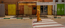 A woman in traditional dress walking in a street in Mhamid, Morocco<br /> <br /> (c) Andrew Wilson | Edinburgh Elite media