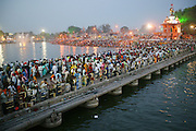 A crowd gathers before dawn on a bridge over the Shipra River which flows through the holy city of Ujjain, in the central Indian state of Madhya Pradesh during the Hindu festival of Kumbh Mela. Every 12 years, millions of devout Hindus celebrate the month-long festival of Kumbh Mela by bathing in the Shipra's holy waters. Hundreds of ashrams set up dusty, sprawling camps that stretch for miles.