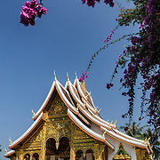 Haw Pha Bang (or Palace Chapel) building framed by purple flowers at the Royal Palace Museum in Luang Prabang, Laos. The chapel sits at the northeastern corner of the grounds. Construction started in 1963.