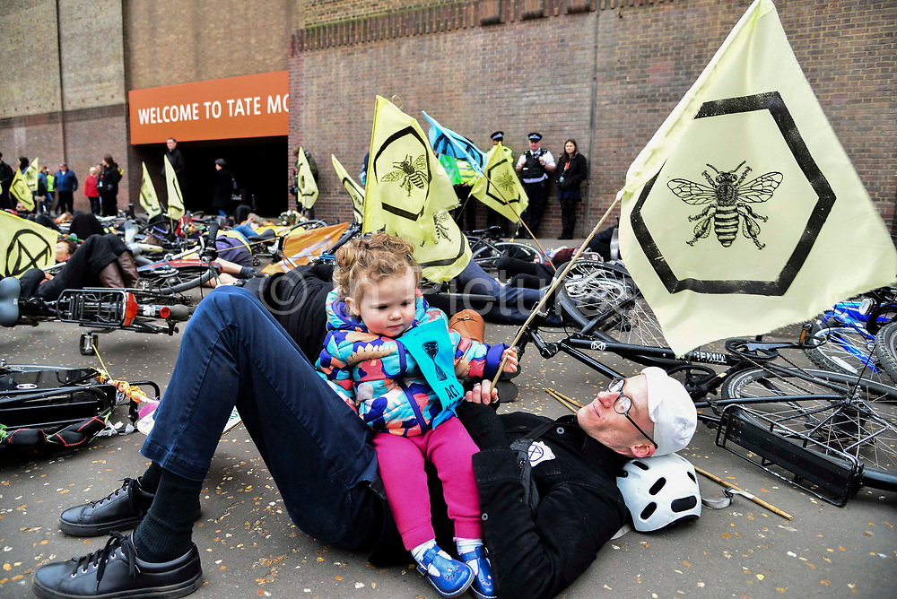 Iro,19 months old attends a die in demonstration by cyclists from  Extinction Rebellion at Tate Modern called XR Critical Swarm on 27th April 2019 in London, England, United Kingdom. The action aims to highlight the global decline in the bee population and the sudden eradication of bee colonies known as Colony Collapse disorder. The climate change activist group are targeting the Tate who they claim, built their fortune on sugar cane production from colonial exploitation of enslaved Africans, European invasion and exploitation of land in West Indies and South America.
