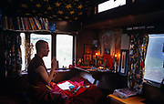 Surrounded by books and holy relics, a monk follower of Tibetan-Buddhism engages in Puja, or prayer, at the Kagyu Samye Ling Monastery and Tibetan Centre in Eskdalemuir, Scotland. This young western man wears traditional Tibetan monk's clothes, prays in a caravan adapted to become a woodland home in the woodland near the Centre. He is a western visitor, many of whom have had a troubled youth and are sometimes escaping a criminal past, who arrive in the Scottish wilderness for isolated Retreat periods, for short-term spiritual relaxation or to follow Tibetan teaching methods for discovering inner-peace, through prayer and meditation. This Tibetan Buddhist complex associated with the Kagyu school celebrates its 40th anniversary in 2007.