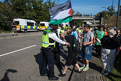 London, UK. 8th September, 2021. Metropolitan Police officers line up in front of human rights activists as a convoy of trucks delivers military equipment to ExCeL London for the DSEI 2021 arms fair. The third day of week-long Stop The Arms Fair protests outside the venue for one of the world's largest arms fairs was themed around demilitarising education.