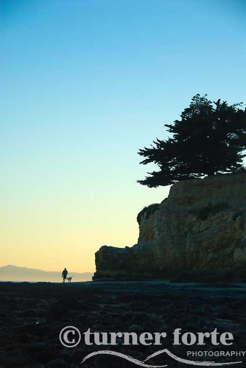 At sunset, a man walks his dog on Leadbetter Beach, Santa Barbara, California.