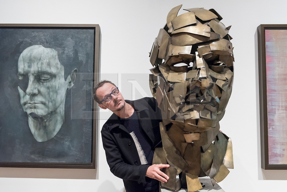 """© Licensed to London News Pictures. 07/12/2017. London, UK.  Artist Jonathan Yeo stands with his work """"Homage to Paolozzi"""", 2017, created using Google's Tilt Brush virtual reality software at a preview of """"From Life"""", a special exhibition at the Royal Academy examining what making art from life has meant to artists throughout history and how the practice has evolved as technology opens up new ways of creating artworks.  The exhibition runs 11 December to 11 March 2018.  Photo credit: Stephen Chung/LNP"""