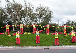 """© Licensed to London News Pictures;29/08/2020; Bristol Airport, Lulsgate Bottom, UK. """"The Landing Crew"""" dressed as aircraft handlers take part in a Common Ground with Extinction Rebellion protest at Bristol Airport against plans to expand the airport and against the airport's decision to appeal against a refusal by North Somerset Council over the expansion plans. This is on the second day of a bank holiday weekend of protest across the UK by Extinction Rebellion. XR are protesting in Bristol and other cities in the UK against climate change, leading up to a protest in London starting on 01 September. XR say that despite clear scientific evidence of the deadly climate and ecological emergency, the UK government are refusing to take the urgent action needed to avoid mass extinction. XR say we need politicians to support the Climate and Ecological Emergency Bill. During the coronavirus covid-19 pandemic, climate change is being forgotten but it is still an emergency that is happening, the elephant in the room. Photo credit: Simon Chapman/LNP."""