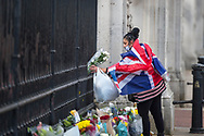 A lady with a Union Jack flag wrapped around her lays flowers in memory of Prince Philip The Royal Highness the Duke of Edinburgh, London on 9 April 2021.