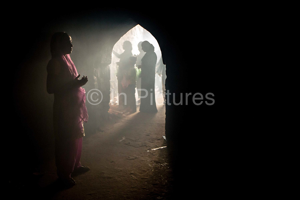 A woman worships in the ruins of the Feroz Shah Kotla Fort In New Delhi, India. In the niches and alcoves of its stone walls, believers - both Hindu and Muslim - pray, light candles and write letters to djinns supernatural creatures of Islamic mythology made of fire and ask for their wishes to be granted.