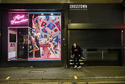 © Licensed to London News Pictures. 20/03/2020. London, UK. A staff member exits Crosstown in Soho after shutting up shop. The West End was left unprecedentedly empty on Friday night following the government's announcement that all bars, pubs and restaurants must be closed immediately in the latest step to curb the coronavirus outbreak.  Photo credit: Guilhem Baker/LNP