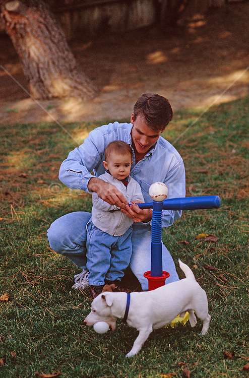 father teaching his son how to hit a baseball as a dog walks by with a ball in his mouth