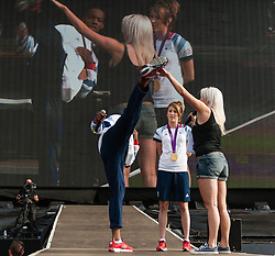 © Licensed to London News Pictures. 11/08/2012. London, UK.  Jade Jones and Lutalo Muhammed of the Team GB UK Taekwondo team who won Gold and Bronze respectively in the London 2012 Olympics.   Jade and Lutalo are onstage at Hyde Park to greet fans and show off their medals.  Here Lutalo shows off a high kick.  Photo credit : Richard Isaac/LNP