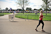 CENTRAL LONDON. A Woman jogs past the line of Pilgrims waiting to gain entry to the vigil. Crowds of Londoners, visitors and pilgrims visit Hyde Park,London, for the visit of Pope Benedict XVI on 17/18th September 2010. It is estimated that 80,000 people will flock to see the Pontiff during his visit to the capital. 18th September 2010.STEPHEN SIMPSON.