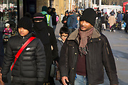 People from various ethnic backgrounds around the market on Whitechapel High Street in East London. This area in the Tower Hamlets is predominantly Muslim with just over 50% of Bangladeshi descent. This is known as a very Asian and multi cultural part of London's East End. Family with the wife wearing a Niqab.