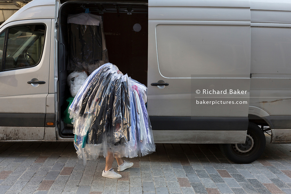Emerging from his van, a dry cleaning contractor gathers many items of freshly-cleaned business clothing and delivers to a nearby address in the City of London - the capital's financial district, on 10th October 2018, in London, England.