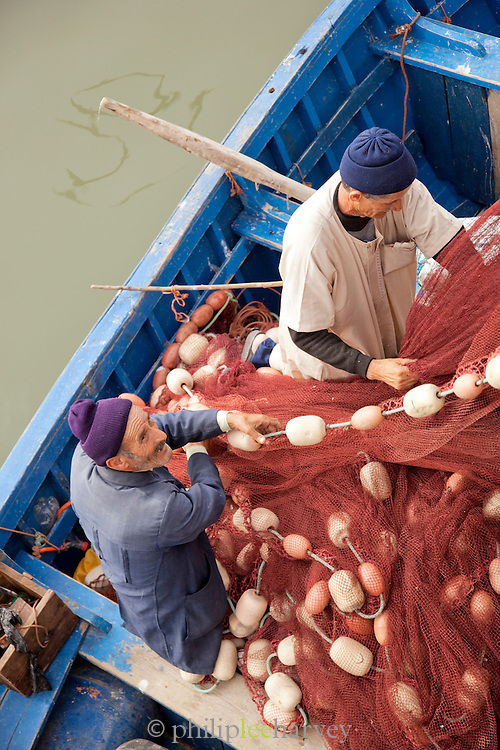 Fishermen sort through their nets in the dock of Essaouira in Morocco