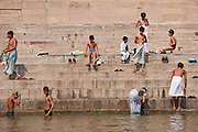 Indian Hindu pilgrims men and boys bathing in The Ganges River by steps of the Ghats in Holy City of Varanasi, Benares, India