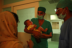 A doctor takes an ill baby to be operated on at the Children's Hospital at the Pakistan Institute of Medical Sciences in Islamabad, Pakistan, Sept. 18, 2007.