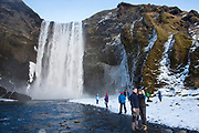Tourists taking selfie photograph at spectacular Skogar waterfall - Skogarfoss - in South Iceland with gushing glacial melting waters