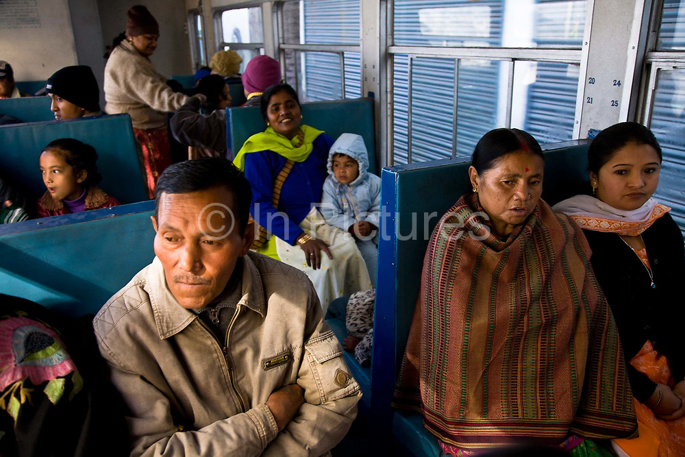 """Local passengers  travel from Darjeeling railway station down to the   various stations heading to Siliguri.  The Darjeeling Himalayan Railway, nicknamed the """"Toy Train"""", is a narrow-gauge railway from Siliguri to Darjeeling in West Bengal, run by the Indian Railways. It was built between 1879 and 1881 and is about 86 km long. The elevation level is from about 100 m at Siliguri to about 2200 m at Darjeeling. It is still powered by a steam engine and travels daily between the two towns, as well as a shorter 32 Km route to Kurseong.  It is now classed as a World Heritage Site by UNESCO. India."""
