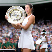 LONDON, ENGLAND - JULY 15:  Garbine Muguruza of Spain with the winners trophy after victory in the Ladies Singles final as Venus Williams of The United States walks back to her seat with the runners up trophy in the background during the Wimbledon Lawn Tennis Championships at the All England Lawn Tennis and Croquet Club at Wimbledon on July 15, 2017 in London, England. (Photo by Tim Clayton/Corbis via Getty Images)