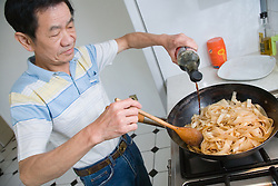 Man adding soy sauce to noodles,
