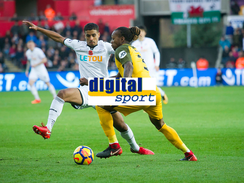 Football - 2017 / 2018 Premier League - Swansea City vs. Brighton & Hove Albion<br /> <br /> Gaëtan Bong of Brighton and Hove Albion challenged by Kyle Naughton of Swansea City , at The Liberty Stadium.<br /> <br /> COLORSPORT/WINSTON BYNORTH