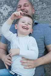 Son with father having fun lying on carpet