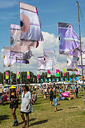 Flags fly in the main arena.  WOMAD 2014, festival of world music and dance, Charlton Park, Wiltshire. UK.