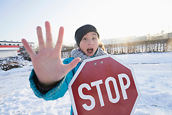 Portrait of girl holding stop sign on snow field
