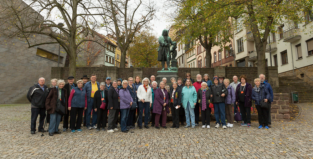 A portion of the tour poses for a group photo in front of a statue of Johann Sebastian Bach outside of his former home in Eisenach, Germany.